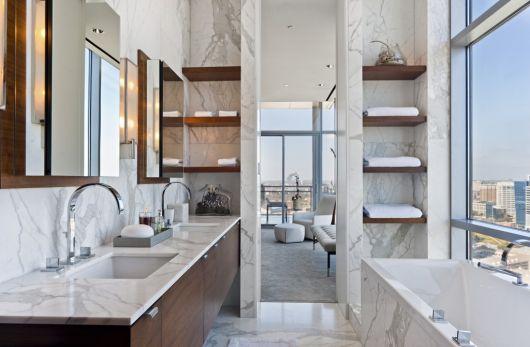 Banheiro espelhado com marmore e prateleiras de madeira.