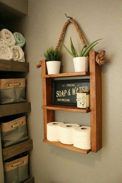 prateleiras de madeira com 3 repartições com itens de banheiro apoiados.