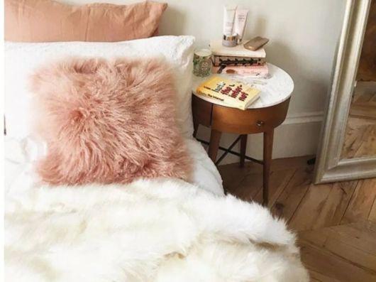 Cama de casal com almofada rosa antigo de pelo