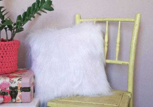 Almofada branca de pelo em cadeira