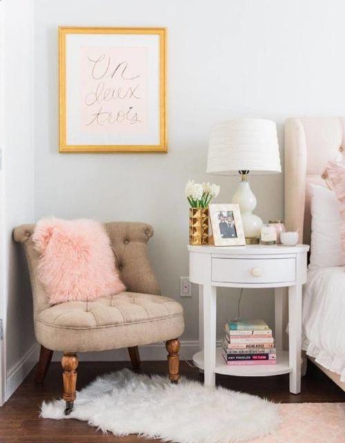 Cantinho de descanso no quarto com poltrona e almofada rosa com pelo