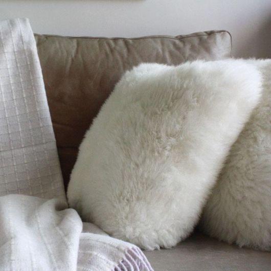 Almofada de pelo branca em sofá bege