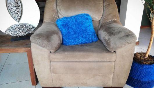 Poltrona marrom com almofada azul de pelo