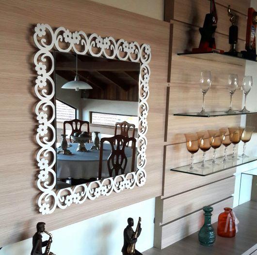espelho quadrado com moldura de madeira vazada.