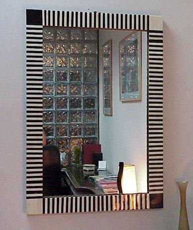 espelho quadrado grande com moldura listrada pintada nas cores preta e branca.