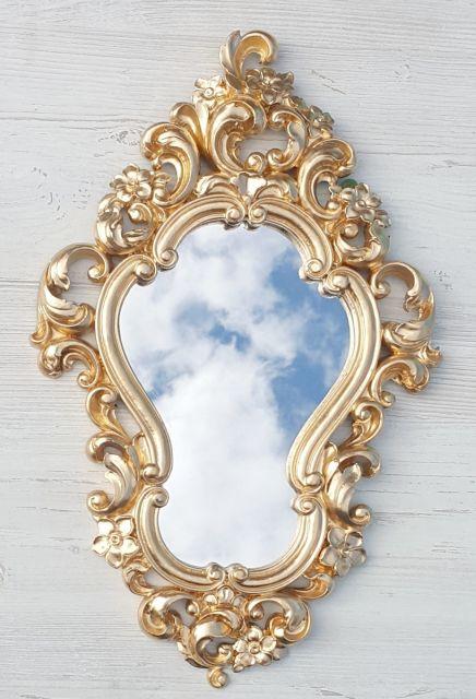 Espelho pequeno com moldura provençal dourada.