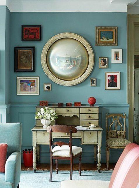 sala azul com espelho redondo de moldura dourada.