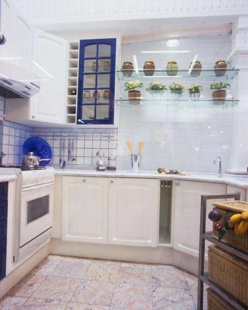 cozinha branca com prateleira de vidro.