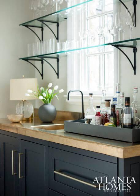 cozinha pequena com armarios pretos e prateleira de vidro.