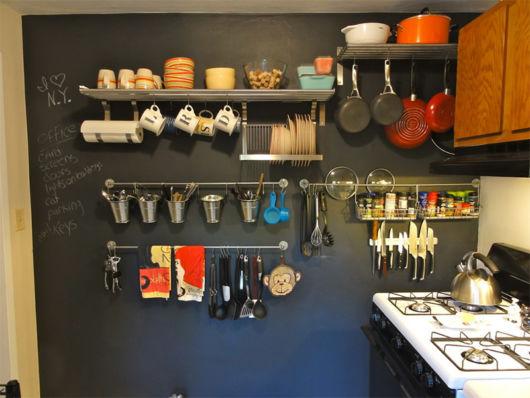Cozinha preta com prateleiras.