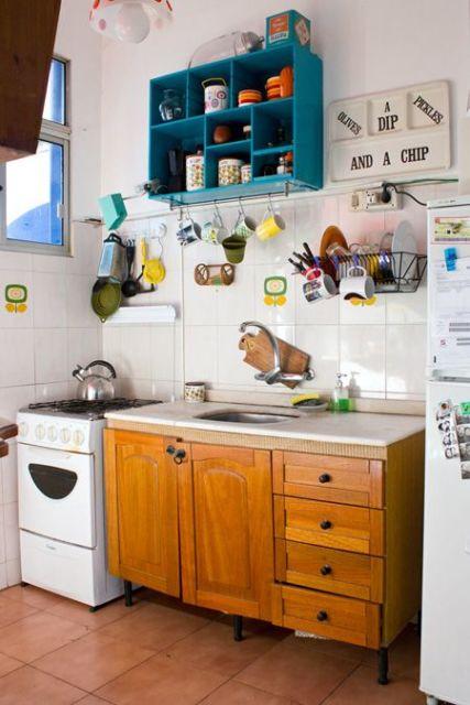 Cozinha branca pequena com prateleira nicho azul.