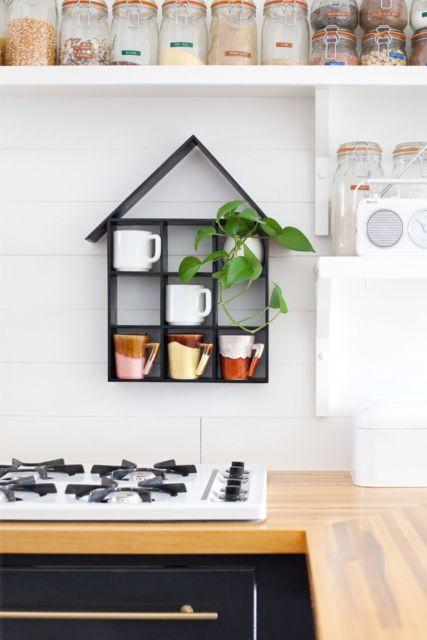 Cozinha branca com prateleira casinha preta de parede.