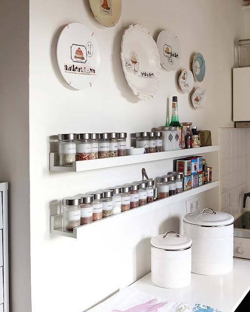 Prateleiras brancas compactas em parede branca de cozinha pequena.