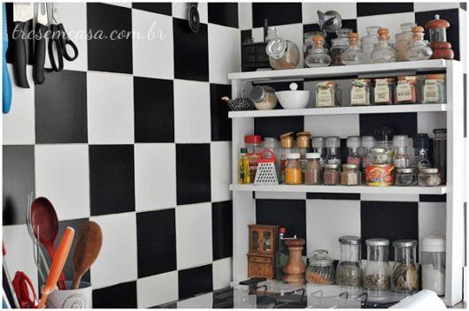 cozinha preta e branca com prateleiras para temperos.