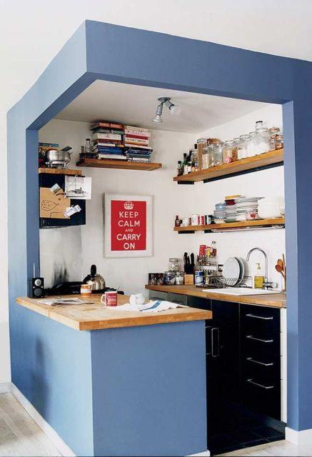 cozinha americana branca com roxo e prateleiras compactas.