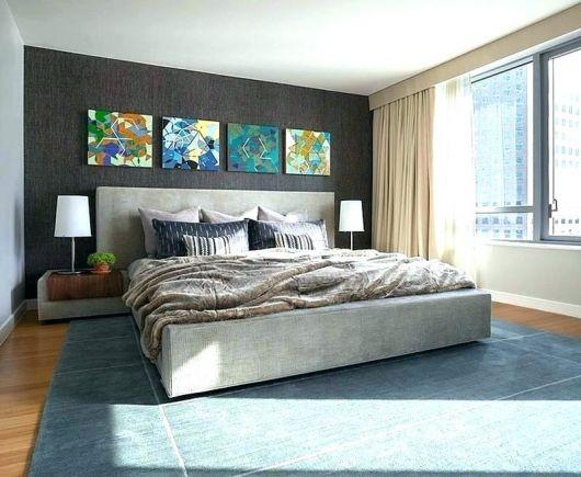 Quatro quadros coloridos acima da cama, destacando entre as paredes sóbrias