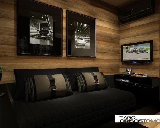 Os quadros pretos em modelo sóbrio combinaram bastante com a parede de madeira