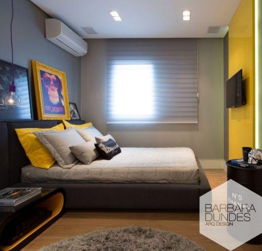 O quadro com moldura amarela combina com a parede em tom único e os travesseiros