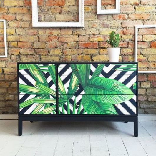 Móveis preto com adesivo de folhas verdes.