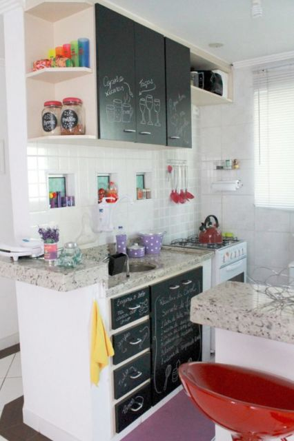 Cozinha com azulejos brancos e móveis pretos.