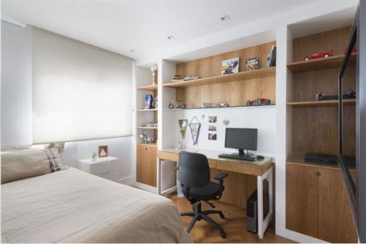A escrivaninha de madeira no quarto é funcional e bonita