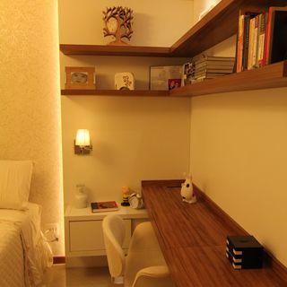 Quarto decorado com escrivaninhas, bem como prateleiras de madeira