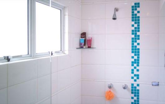 banheiro com prateleira de vidro