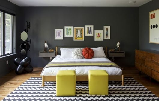 Parede preta e detalhes em cores quentes, como os puffs amarelos