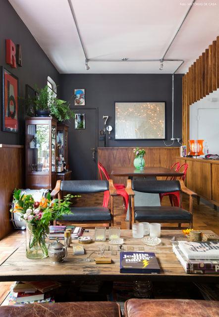 O complemento da parede preta com os detalhes em madeira dão um ar sofisticado ao ambiente