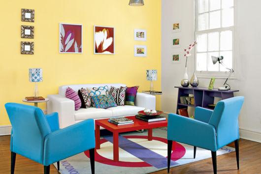 A parede amarela ilumina a sala, os móveis em cores vibrantes ajudam a deixar o ambiente equilibrado