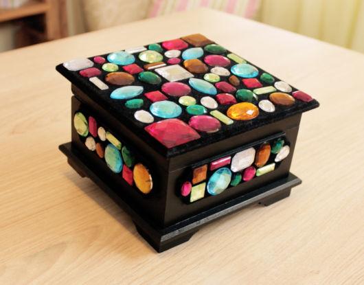 As pedras coloridas transformam a caixa de madeira