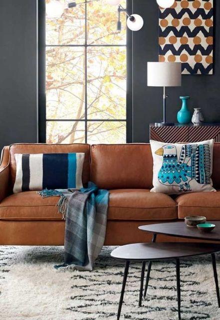 As paredes escuras proporcionam conforto com sofá marrom