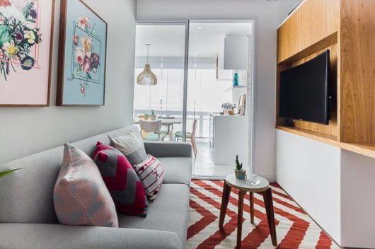 Sala pequena de TV com branco, que ajuda a expandir o espaço