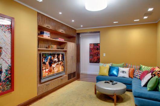 Combine o amarelo com painel de madeira para dar elegância sala de tv