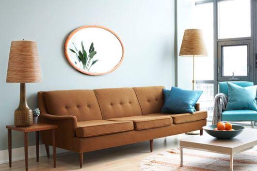 Sofá marrom claro com parede azul clara
