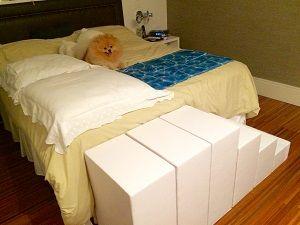 Escada para cachorro do lado de uma cama de casal.