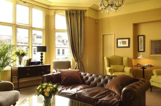 Com um sofá marrom de couro você dá um toque especial na sala amarela