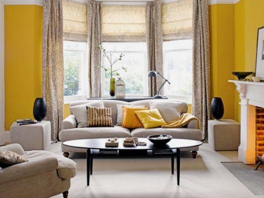 Dica de sala contemporânea com paredes amarelas e móveis cinzas