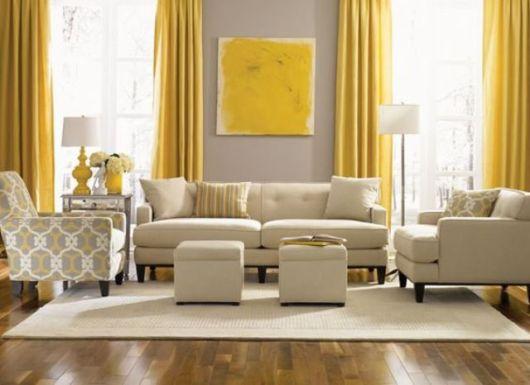 A cortina amarela, bem como o quadro ajudam a renovar a sala