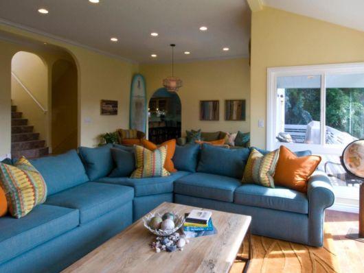 Sala espaçosa com as paredes amarelas o sofá em de canto azuk