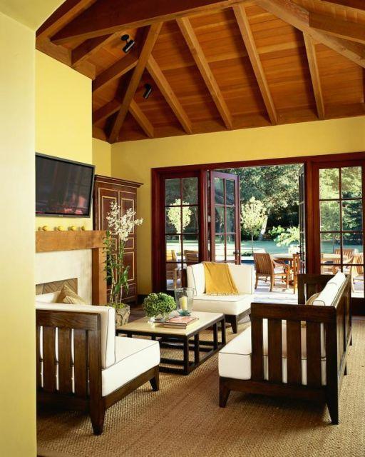 Sala amarela com a mobília de madeira, naturalmente marrom