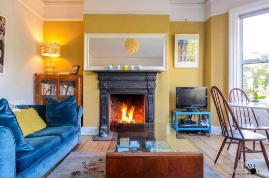 Sala moderna com parede amarela e móveis azuis