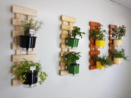 Vários pallets na parede com dois vasos