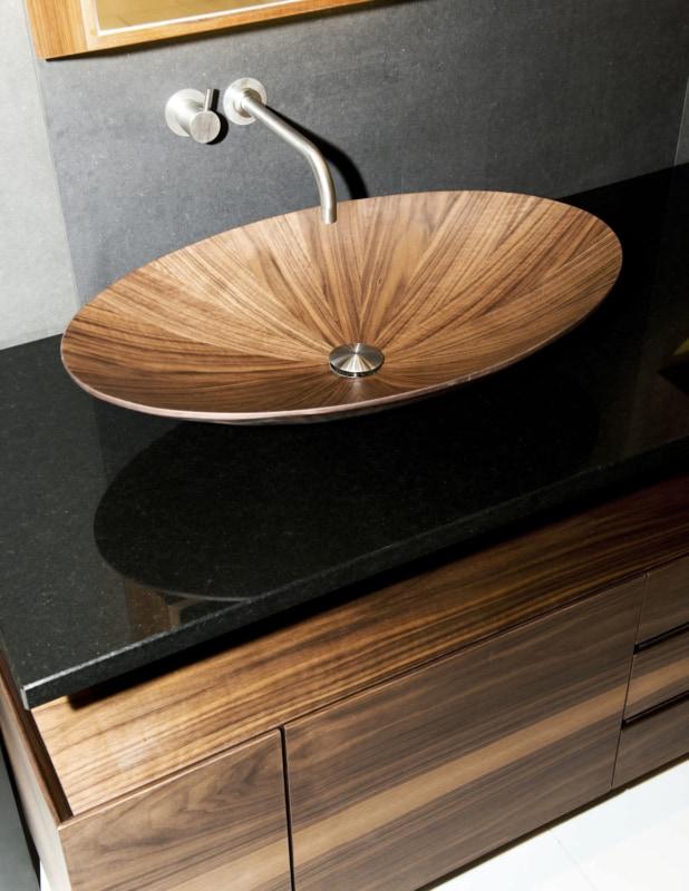Cuba de madeira oval diferente sobre bancada de granito preto
