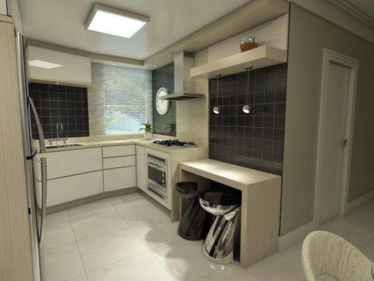 As cores sóbrias se destacam em meio a diversos projetos de cozinha para apartamento pequeno planejada