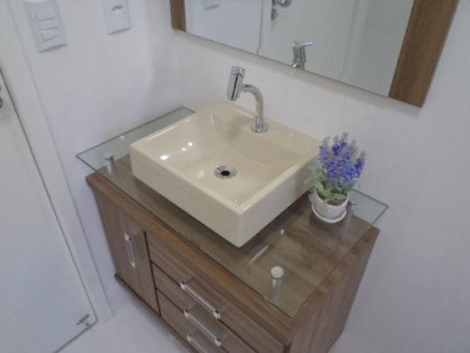 Luxo e requinte nessa junção de cuba quadrada com balcão de vidro e armário de madeira