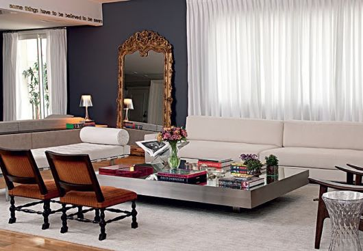 A moldura marrom retrô combina bastante com a parede preta e os detalhes industriais na decoração