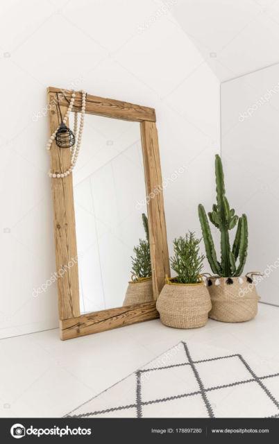 Espelho grande de madeira junto aos vasos decorativos