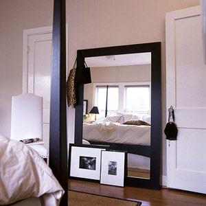 O espelho deve se adaptar fielmente à decoração do seu quarto, como essa versão com moldura preta