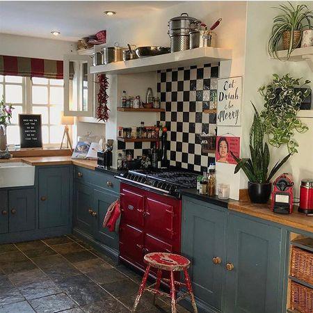 Uma cozinha antiga com o fogão retrô vermelho em meio aos balcões dos armários
